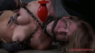Brown head bitch gets her firm nipples squeezed hard in BDSM video image