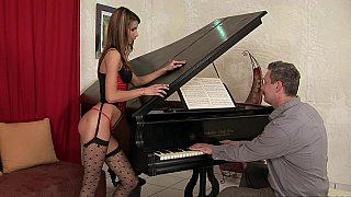Young babe in lingerie fucked by an old guy on a piano image