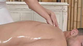 Sexy masseuse oils and wanks_cock in massage room image