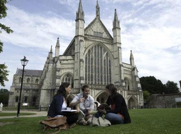 Students sitting on the grass outside Winchester Cathedral