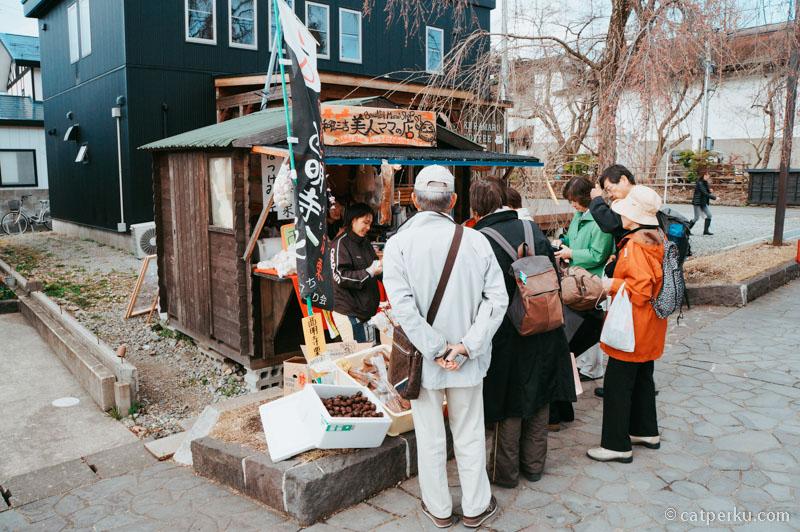 Penjual oleh-oleh setempat dikerubungi para turis lokal orang Jepang.