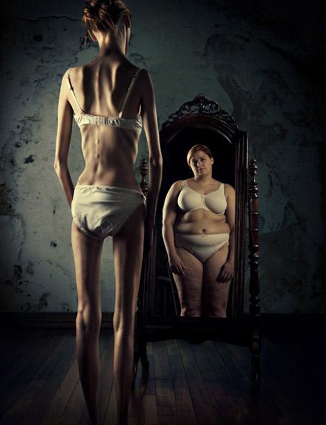 mulher anorética olha-se no espelho e vê um reflexo de si gorda