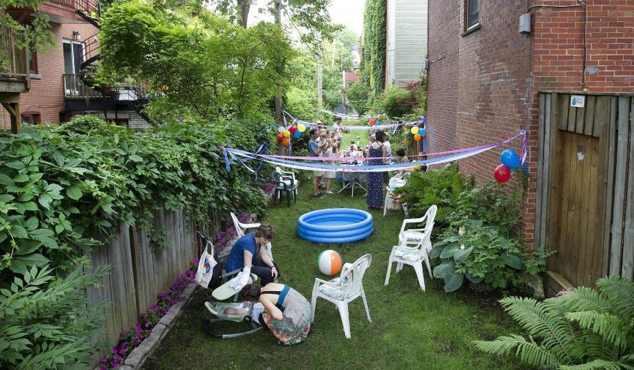 This photo shows a long narrow patch of grass between two brick apartment buildings. Adults and small children appear to be having a party, seated on white plastic chairs, with a kiddie pool on the ground, and colorful streamers and balloons tied to the building wall and the fence at the left of the frame. Leaves, vines, and trees are visible over the top of the fence.