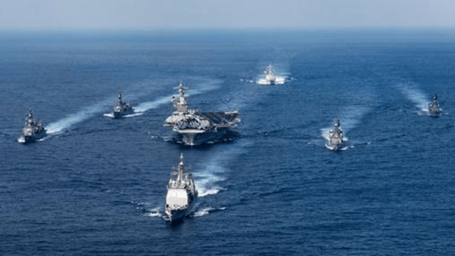 A group of military ships in the water  Description automatically generated with low confidence