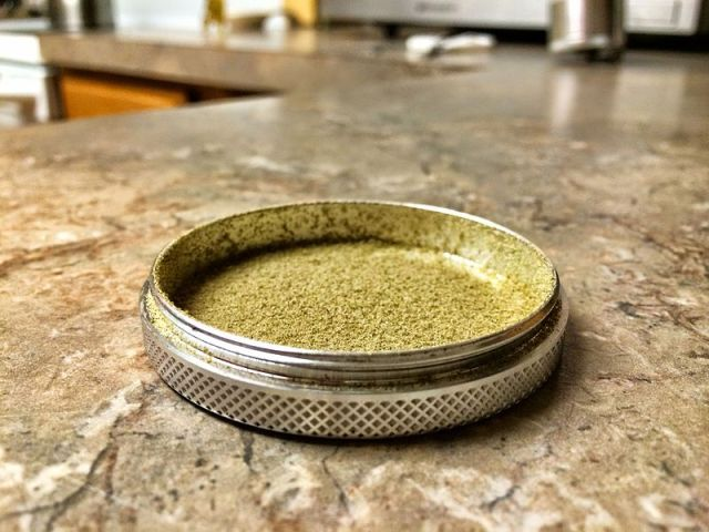 The bottom part of a grinder with a layer of kief accumulated