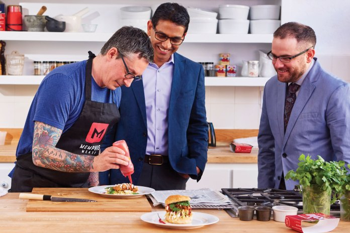 Photo of man preparing food while two others look on