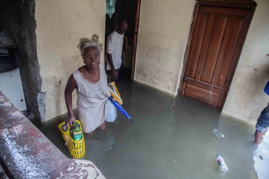 Le persone trasportano oggetti, camminando attraverso l'acqua di inondazione profonda fino al ginocchio all'interno di una casa.