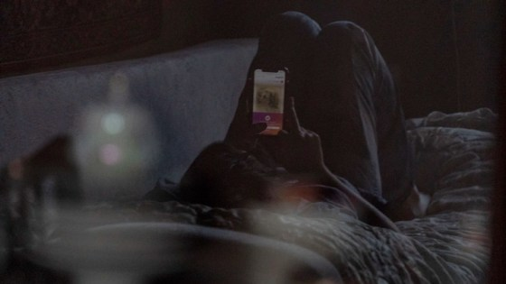 A teenager lying on a couch, looking at a cell phone.