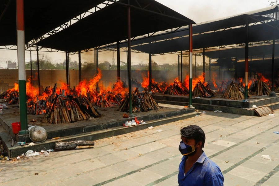 More than a dozen funeral pyres burn side by side in an open crematorium.