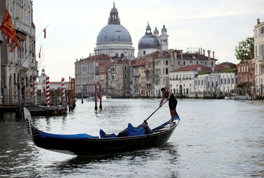 A gondolier rows on Venice's Grand Canal.
