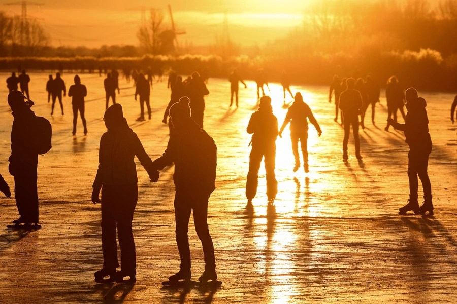 Dozens of people skate on a broad frozen surface at sunset.