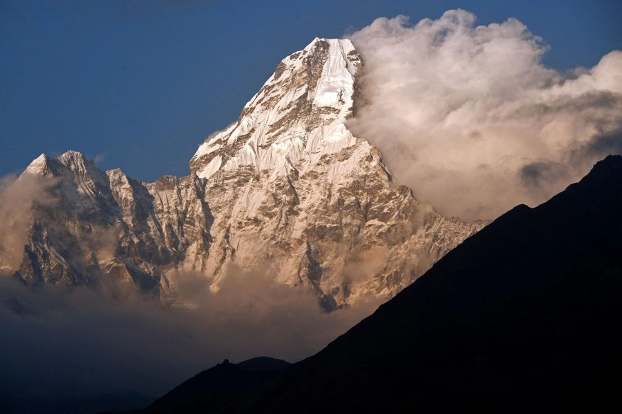 A tall mountain is seen among clouds.