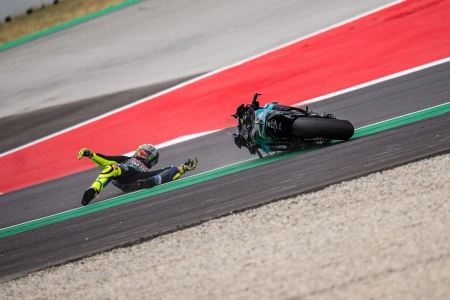 A motorcycle rider and his motorcycle slide across a track after a crash.
