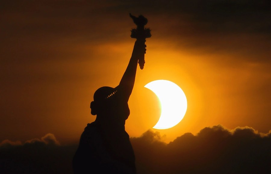An eclipsed sun rises behind the Statue of Liberty.