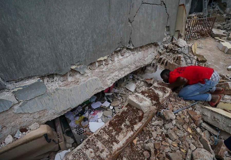 Una persona si inginocchia guardando sotto un edificio gravemente danneggiato.