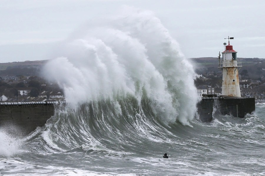 A person swims and takes photographs near large waves crashing against a pier.