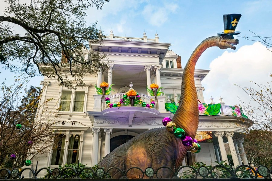 A large statue of a dinosaur wears a beaded necklace and top hat, standing in front of a decorated house.