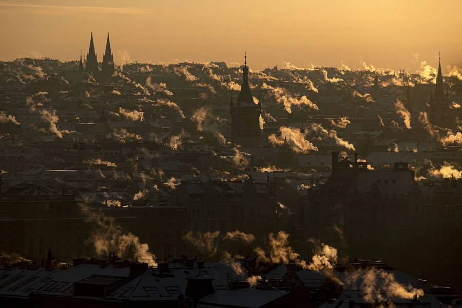 Smoke rises from many chimneys seen in a broad view of Prague.