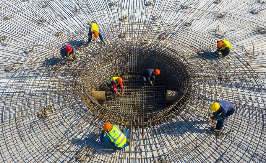 Construction workers attend to a circular section of a construction project.