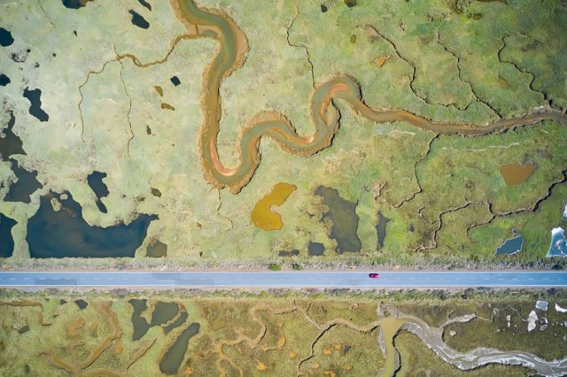 An aerial view of a straight road cutting across wetlands.