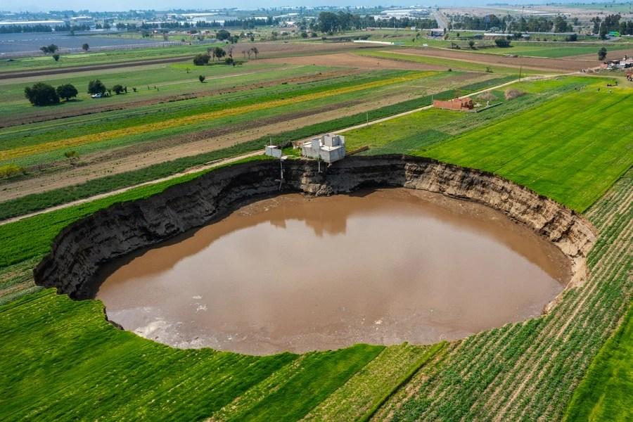 A large sinkhole is seen alongside a house in a farm field.