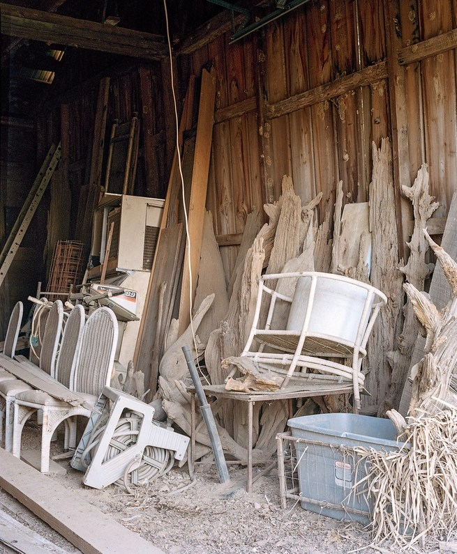 photo of inside the barn, with dusty furniture and other storage
