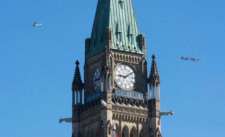 A plane flies past the Peace Tower in Ottawa trailing a sign protesting the TPP agreement. (THE CANADIAN PRESS/Adrian Wyld)