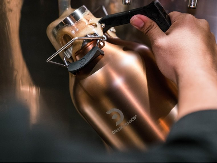 A man pours a fresh beer from a silver DrinkTanks perfect growler