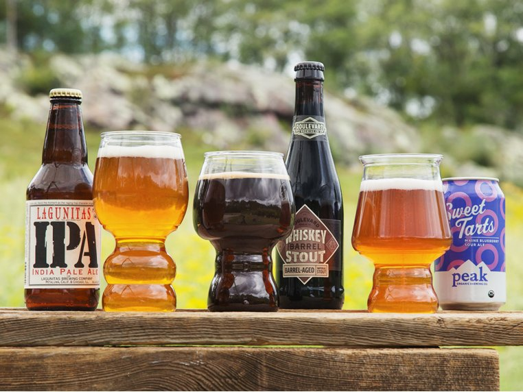 Different bottles of beer sit next to B Cups shatterproof craft beer cups