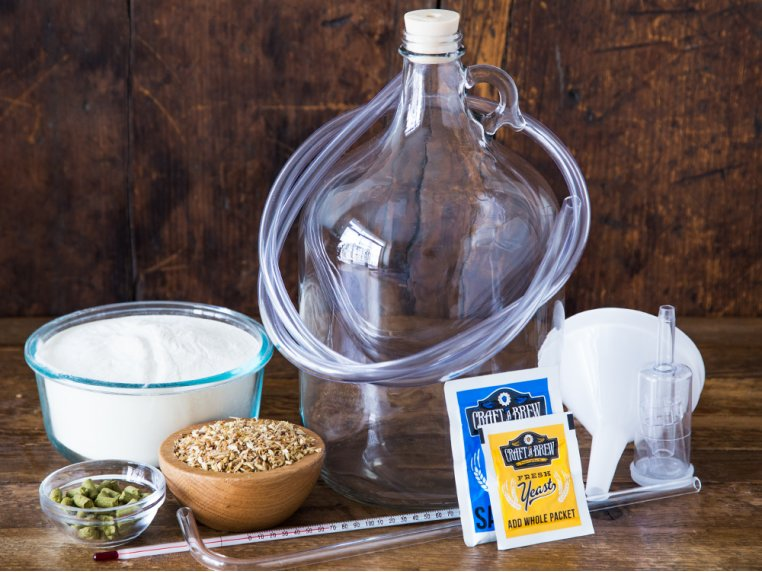 A home brewing kit from Craft A Brew sits on a table with all the beer brewing supplies