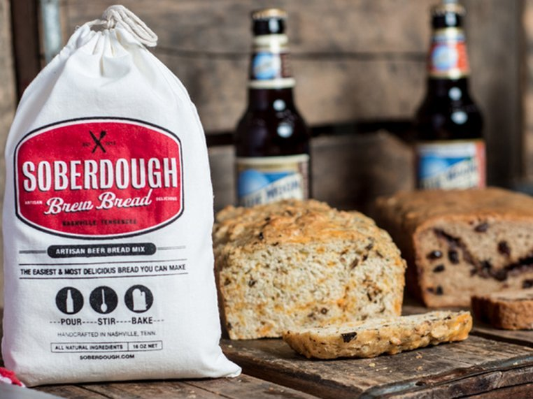 A sack of SoberDough bread mix sits next to two loaves of beer bread