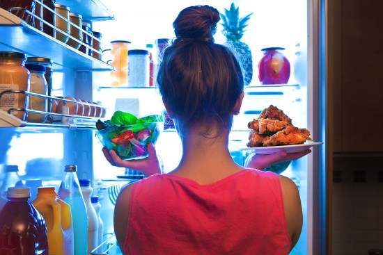A young woman standing in front of an open refrigerator holds a bowl of salad in one hand and a plate of fried chicken in the other.