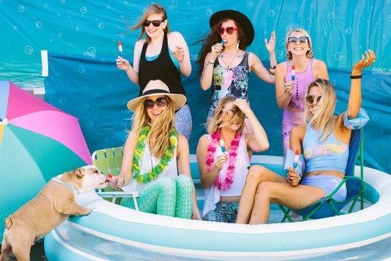 Women have a pool party for a photoshoot.