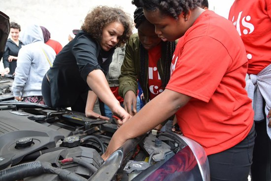 A woman mechanic instructs other women on car repair.