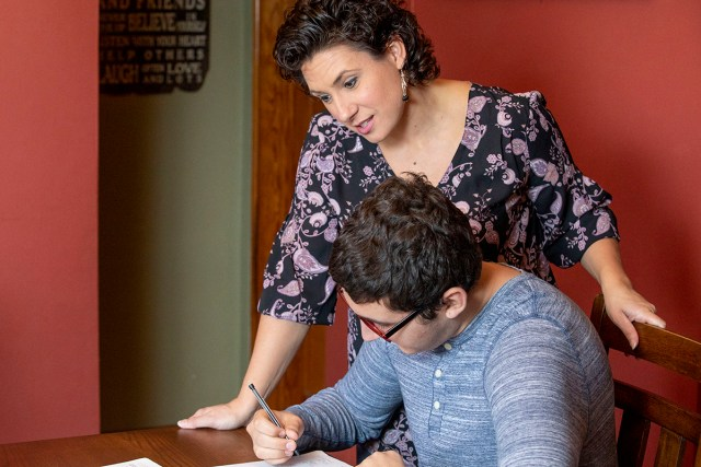 A woman helps her teenage son with homework.