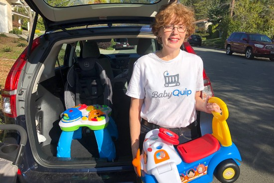 Trish McDermott poses with baby gear in front of the trunk of her car