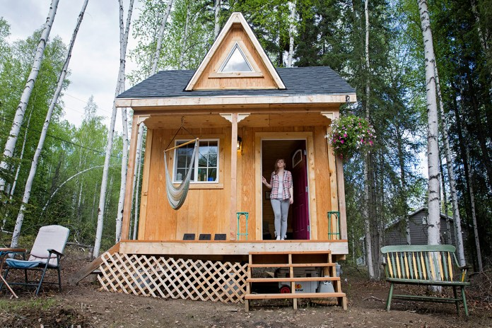 A woman stands in the doorway of her tiny home.