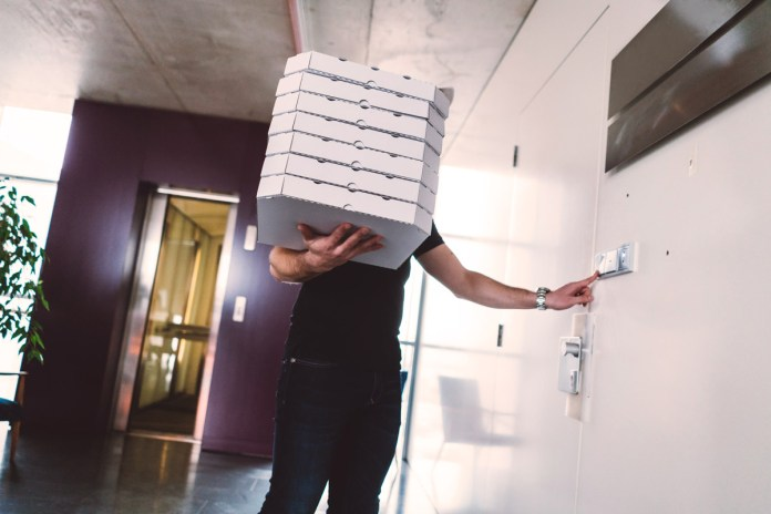 A man holds many pizza boxes as he waits for the elevator in the customer's apartment building.