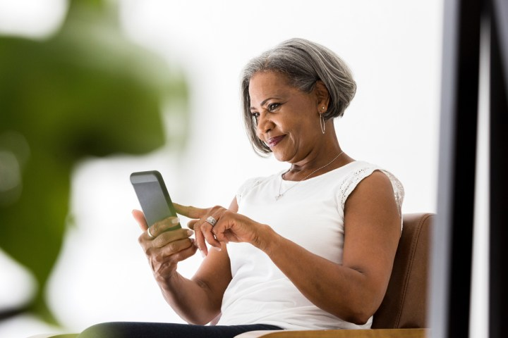 A woman text messages someone on her phone.