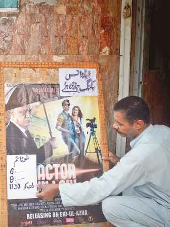 A man puts up a notice announcing showtimes outside a cinema house. Credit: Fahim Siddique, White Star