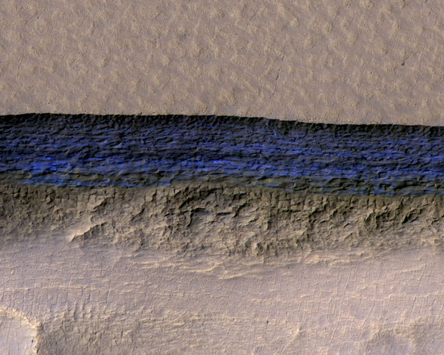 A cross-section of a thick sheet of underground ice is exposed at the steep slope that appears bright blue in this enhanced-color view of Mars from the High Resolution Imaging Science Experiment (HiRISE) camera on NASA's Mars Reconnaissance Orbiter in this image released on January 11, 2018. NASA/JPL-Caltech/UA/USGS/Handout via Reuters