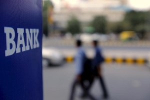 Commuters walk past a bank sign along a road in New Delhi in this November 25, 2015 file photo. Credit: Reuters/Anindito Mukherjee/Files