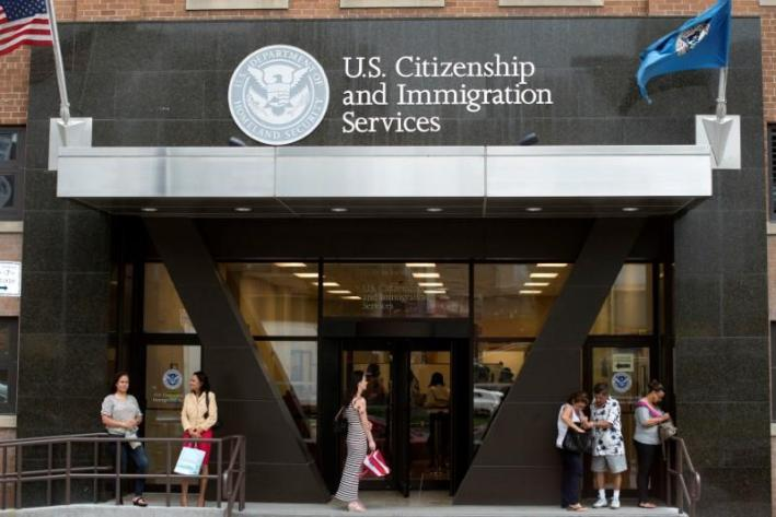 People stand on the steps of the US Citizenship and Immigration Services offices in New York, US on August 15, 2012. Credit: Reuters/Keith Bedford