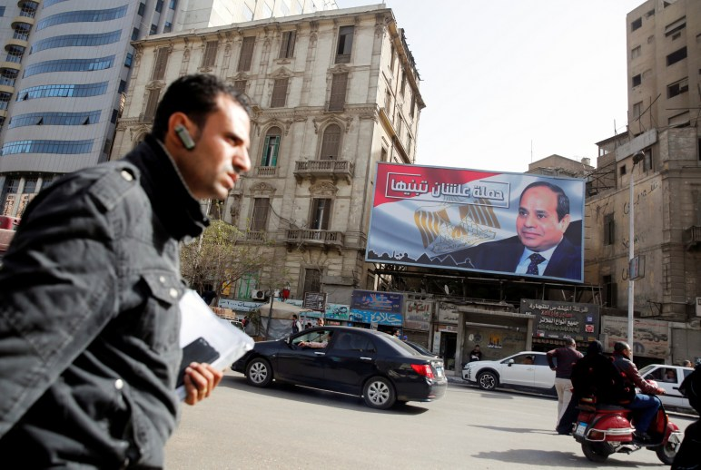 """People walk by a poster of Egypt's President Abdel Fattah al-Sisi from the campaign titled """"Alashan Tabneeha"""" (So You Can Build It) for the upcoming presidential election in Cairo, Egypt, January 22, 2018. Credit: Reuters/Amr Abdallah Dalsh"""