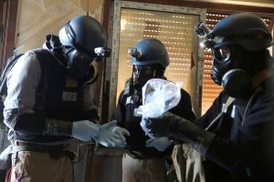 A UN chemical weapons expert, wearing a gas mask, holds a plastic bag containing samples from one of the sites of an alleged chemical weapons attack in the Ain Tarma neighbourhood of Damascus, Syria August 29, 2013. Credit: Reuters/Mohamed Abdullah