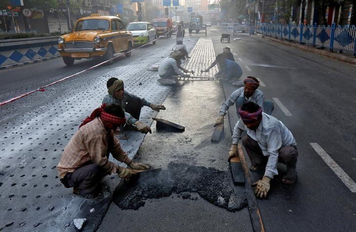 Labourers work at a road construction site early morning in Kolkata February 27, 2017. Credit: Reuters/Rupak De Chowdhuri