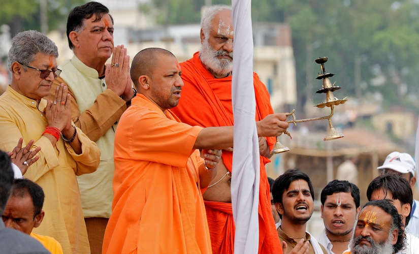 "Adityanath, chief minister of Uttar Pradesh, holds a llamp as he performs ""Aarti"" on the banks of river Sarayu in Ayodhya, India, May 31, 2017. Credit: Reuters/Pawan Kumar"