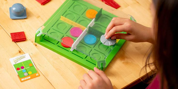 A child playing with ThinkFun Invasion of the Cow Snatchers.