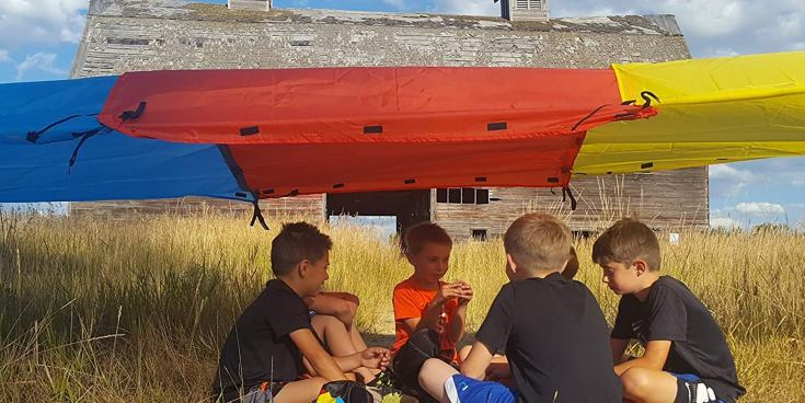 Four children sitting underneath a fort build with a Tote-A-Fort kit.