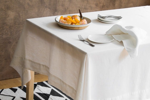 The Rough Linen Smooth Tablecloth On A Wood Table With Plates Cutlery And